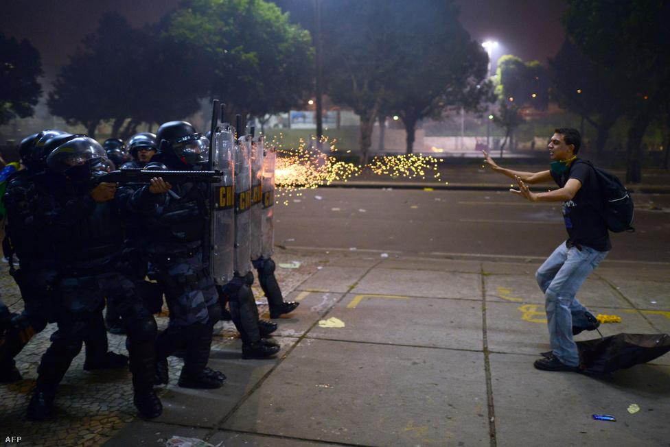 Gumilövedéket vetnek be rohamrendőrök egy tüntető ellen Rio de Janeiróban június 20-án. Brazília jövőre ad otthont a labdarúgó világbajnokságnak, így idén Konföderációs Kupát rendezhetett. Felháborította a tüntetőket, hogy az ország milliárdokat költött a Konföderációs Kupára, a 2014-es futball-vb-re, a 2016-os olimpiára, miközben a rohamos gazdasági fejlődéséért dicsért Brazíliában milliók élnek nyomorban. A tüntetők szerint nem világversenyek kellenek, hanem kórházak és iskolák. Csak a riói olimpiai előkészületek 13 milliárd dollárt emésztettek fel.