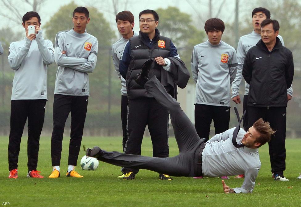 David Beckham elesik, miután megkísérelt elvégezni egy szabadrúgást a vuhani focicsapat edzőpályáján Kínában.