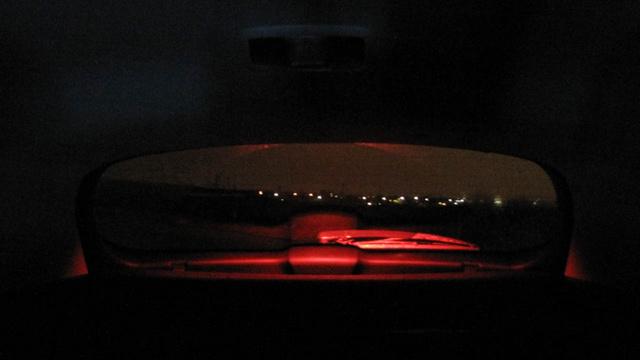 A pótféklámpa vörös fénnyel derít mindent, ami a hátsó ajtón van, talán még a koszt is, ilyenkor az ablaktörlő vörös démonként lebeg a visszapillantóban