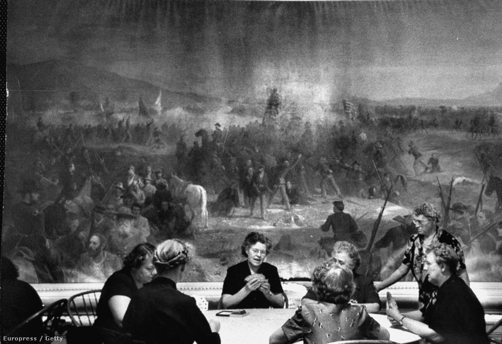 A háttérben egy háborús festmény, a zárt ajtók mögött államférfiak tanácskoznak. Az előtérben pedig a feleségek kártyáznak. 1953, Vermont.