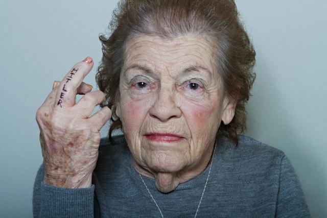 """""""Nem a sorszámom vagyok"""" - ez a szöveg áll a lágereket megjárt idős asszony képe alatt."""