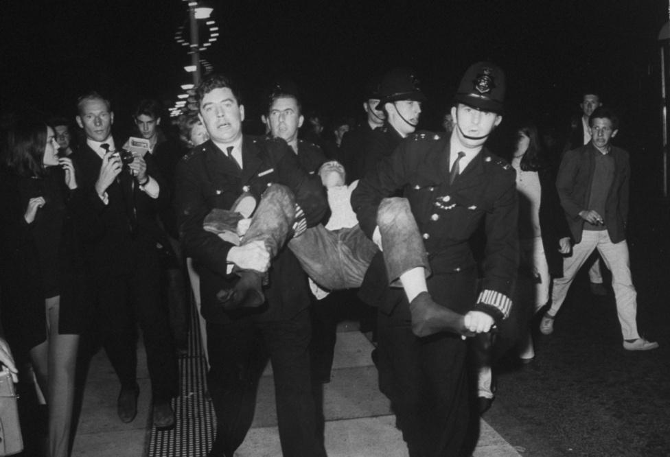 1964, Anglia. Az 1960-as évek nagy ifjúsági összecsapása volt a Mods vs Rockers ellentét, amit a média jól fel tudott fújni. A két csoport véres összetűzései általában rendőri beavatkozást igényeltek, a képen éppen egy rockert tartóztatnak le.