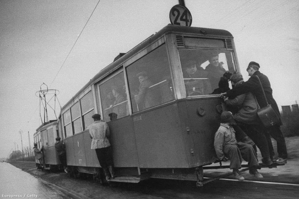 Emberek csüngnek a villamoson Lengyelországban. Úgy látszik, nem tudják, hogy nem szabad az ütközőn utazni.