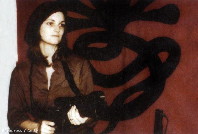 Patty pózol egy fegyverre a SZFH jele plakátja előtt