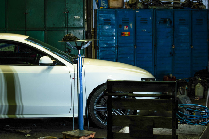 There is a sharp contrast between the pearl white Audi A5 and the workshop. They have worked on Bentleys here, too
