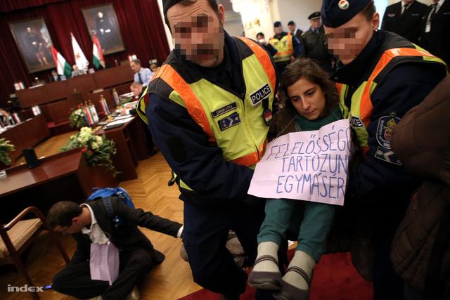 Megjelent a rendőrség, egy erélyes hang a BRFK-tól tájékoztatott, a magatartás súlyosan megzavarja a közgyűlést. Felszólította a tiltakozókat, hogy a termet hagyják el. A rendezvényt feloszlatja.