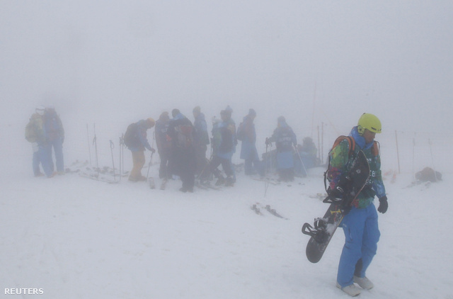 Az elhalasztott snowboard szám résztvevői állnak a sűrű ködben ami ma meghatározta a játékok tempóját