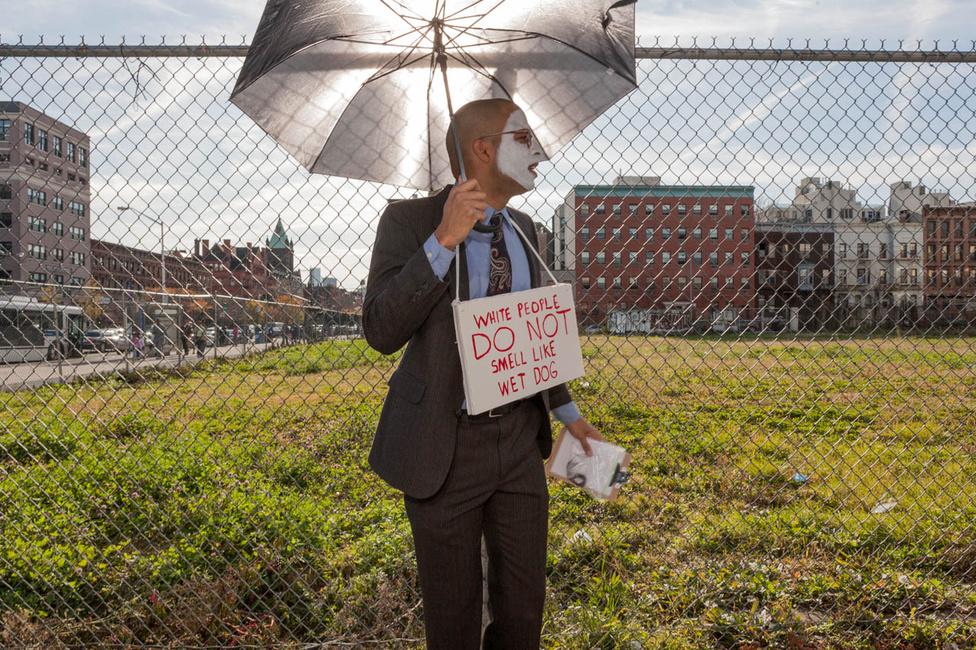 """""""Sokan képzelik azt, hogy ahhoz, hogy olyasmit csináljunk, mint a képek szereplői, ahhoz naplopónak kell lenni. De ennek éppen az ellenkezője igaz: a legtöbbjüknek van munkája, normális élete is, és emellett csinálnak különös dolgokat."""" Ez a maszkos férfi például """"A fehér embernek nincs ázott kutya szaga"""" feliratú táblával pózol egy esernyő alatt."""