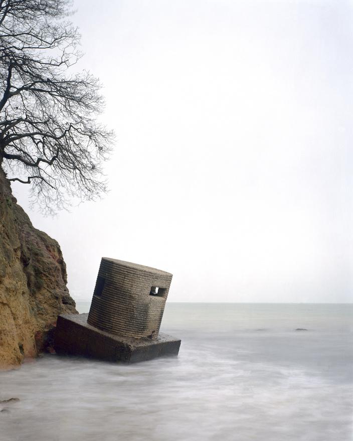 Studland Bay I, Dorset, Anglia                         A képen a 25-ös típusú kiserőd, avagy pillbox egy egész épen megmaradt példánya látszik. Az erőd a Studland-öbölben van, ott, ahol a szövetséges erők a D-napot gyakorolták. Itt derült ki, hogy azok a kétéltű tankok, amik nyugodt tengeren simán leúsztak akár nagyobb távolságot is, nagyobb hullámzás idején pont úgy süllyednek a tengerfenékre, ahogy azt egy harminctonnás tanktól elvárná az ember. Egyes történészek szerint ez a tapasztalat konkrétan megmentette a partraszállást, az eredeti tervekkel ellentétben a tankokat ugyanis a parthoz jóval közelebb eresztették vízre, így egy részük partot is ért, és segített a német erődítmények leküzdésében.