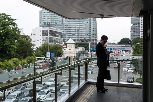 Irodista a mobilját csekkolja Kuala Lumpur belvárosában egy teraszon