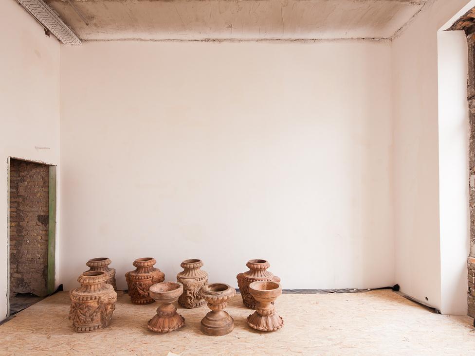 A bazársor tetejét díszítő terrakotta emberfejes vázák itt még a rekonstrukció végét várják. Azóta már a helyükre kerültek.