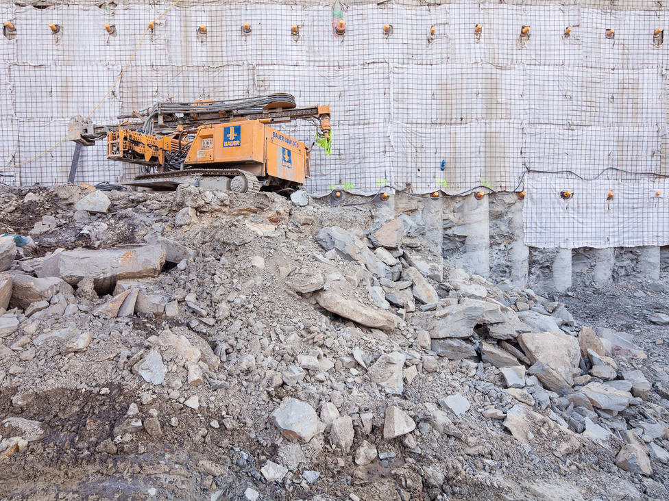 Az építkezést lassította, hogy közel ötméteres tömör márgaréteggel kellett megküzdeni. Ennek a törmelékén áll a képen a munkagép. Mögötte vasbetoncölöpök fogják meg a Várhegy oldalát.