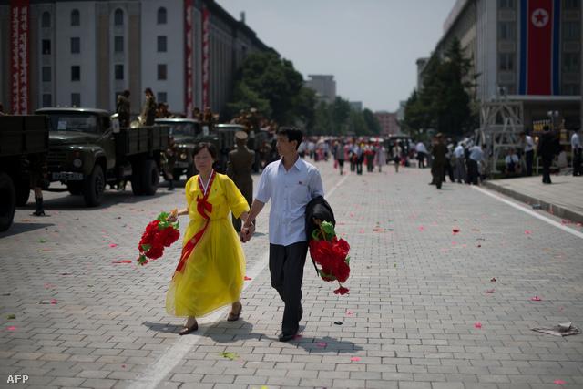 Egy pár sétál kézen fogva egy phenjani katonai parádén.