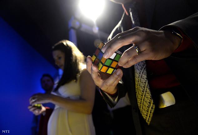 Látogatók próbálják kirakni a bűvös kockát az idén 40 éves Rubik-kocka tiszteletére rendezett Beyond Rubik's Cube című kiállításon
