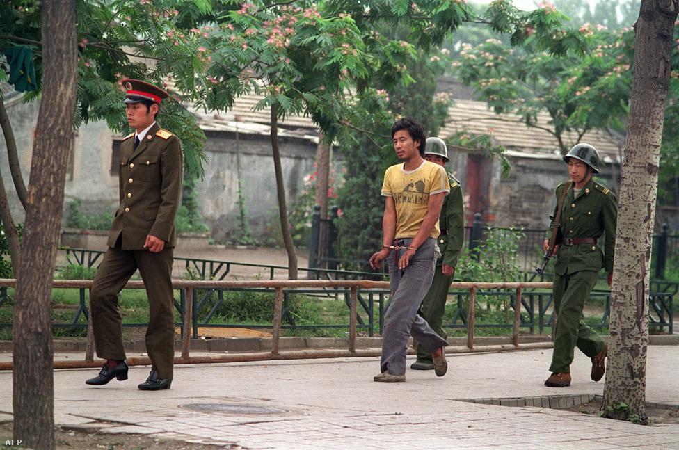 Június 14.: bilincsbe vert férfit vezetnek el kínai katonák, akit azzal gyanúsítottak, hogy részt vett a megmozdulásokban.