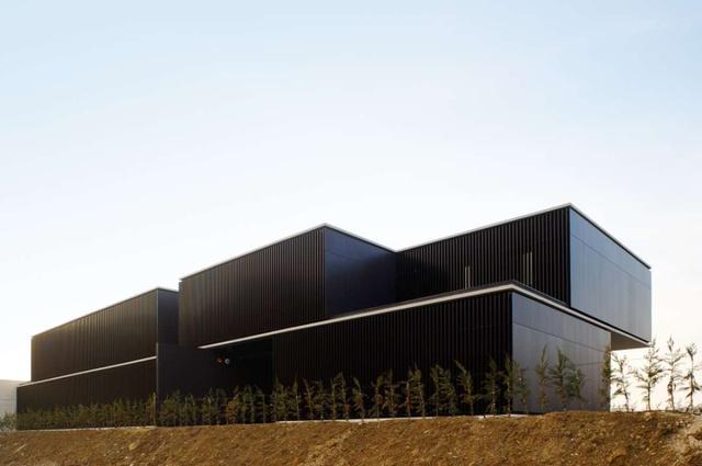 Javier Larraz és építész csapata elegáns, függőleges alumínium elemekkel vonta be az átmeneti otthont, ami első ránézésre egy sivár környezetbe helyezett dobozra emlékeztet, pedig tereinek rendkívül racionális és felhasználóbarát az elosztása.
