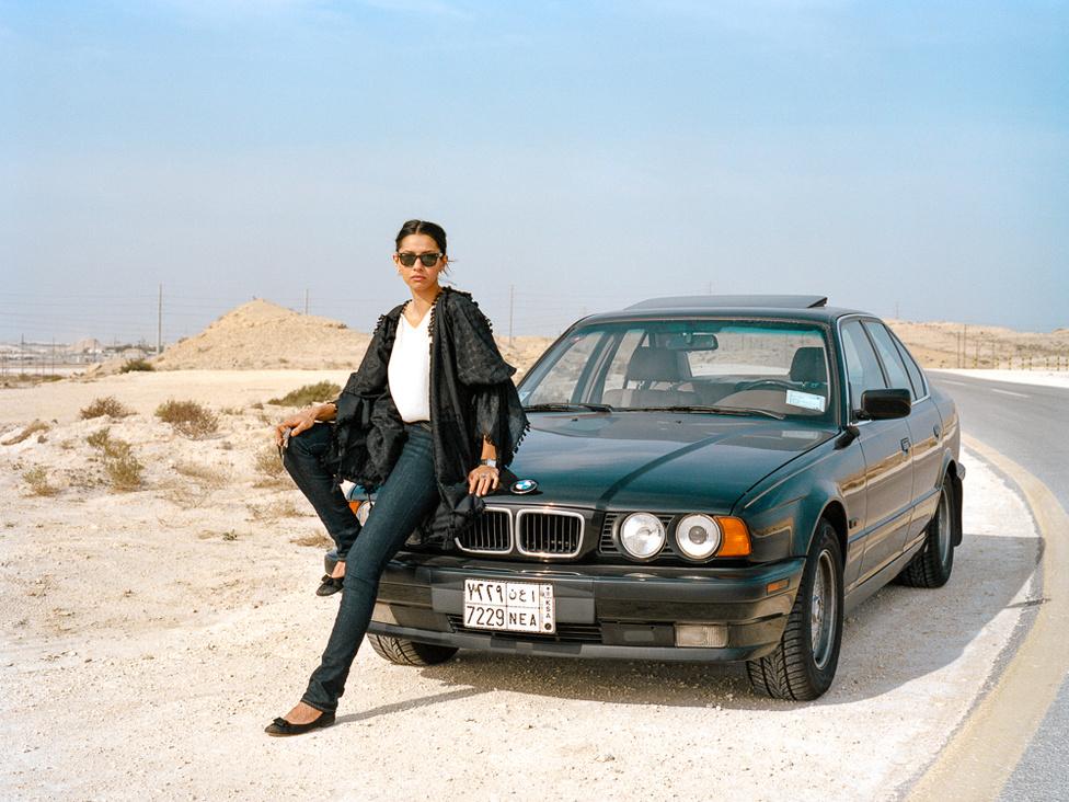 Nő az autójával. A létesítményen belül Szaúd-Arábia más részeivel ellentétben a nők is vezethetnek autót.