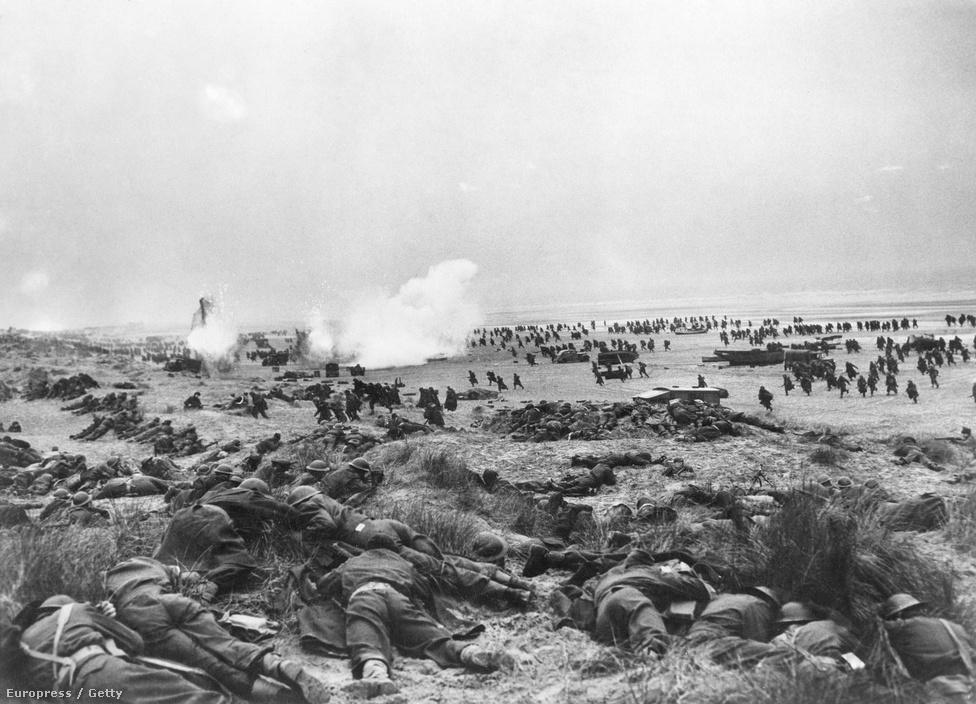 Nem, ők nem a dűnéket ellepő halottak, hanem élők, akik nem akarnak meghalni. Ezért egy gránátbecsapódás (látják a fehér füstöt?) elől igyekeznek magukat minél mélyebbre fúrni a homokba. Június elejére a védelmi gyűrű szűkülésével a német nehéztüzérség is lőtávolba került, ezért a katonáknak már nem csak a bombák miatt kellett aggódniuk.