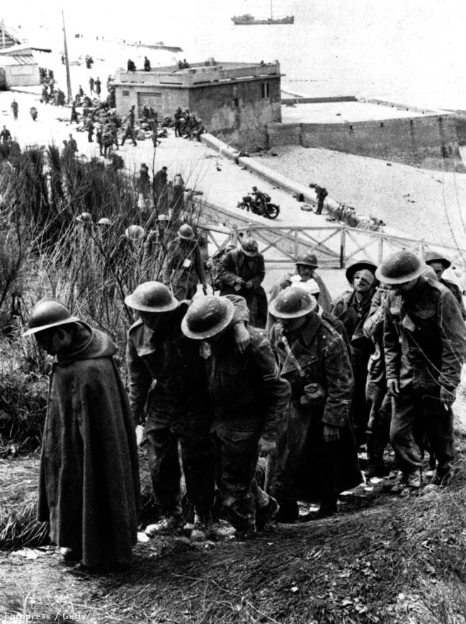 Leharcolt, alakulatuktól elkószált - figyeljék csak meg a legelső katona francia mintájú rohamsisakját! - katonák várnak a sorukra. Nekik legalább nem kellett levánszorogniuk a fövenyre, hanem Dunkirk két hosszú hullámtörőjéről hajózhattak be. A hullámtörők ideiglenes mólóként való alkalmazása nagyon meggyorsította a kimenekítést: 200 ezer ember innen lépett a fedélzetre.