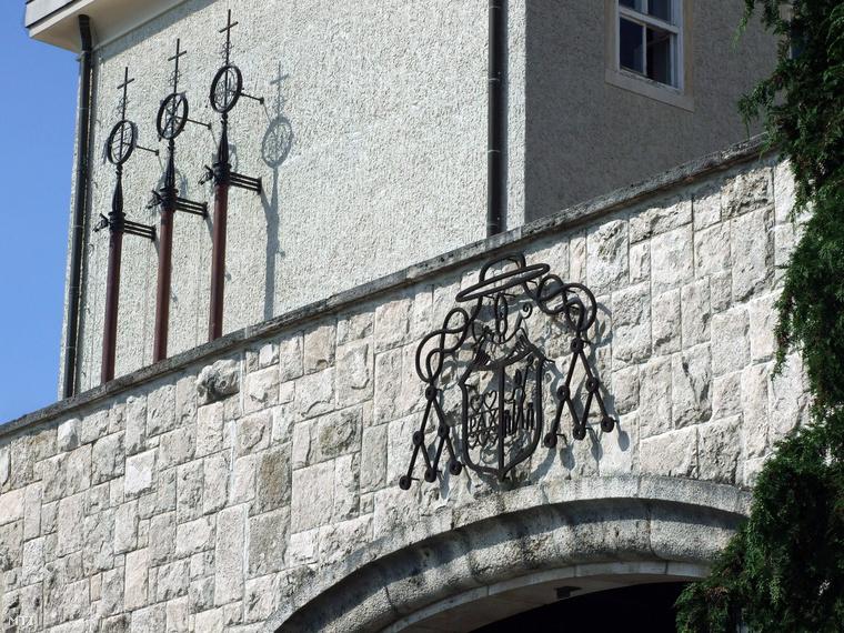 A Pannonhalmi Bencés Főapátság kovácsoltvasból készült címere a Szent Márton-hegyen a műemlék épületegyüttes főbejárata felett.