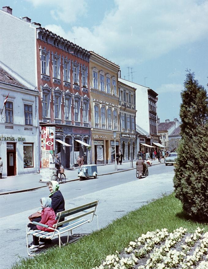 Soproni utcakép 1964-ből. Az utcán látható egy fura szerkezet. És én ezért szeretem ezt a képet. A                         Nyíregyházán készült, motorkerékpár-motoros Szabolcs áruszállítóról ugyanis nagyon kevés eredeti fotó                          maradt fenn, színes pedig szinte egyáltalán nem. 4-5 év alatt alig párszáz Szabolcs készült, utódjából a                          Nyírségből még kevesebb.