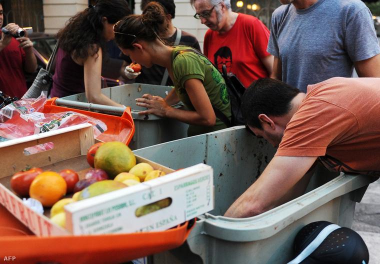 A Comida Basura nevű spanyol aktivistacsoport tagjai ehető élelmiszert válogatnak kukákból egy madridi szupermarket mellett