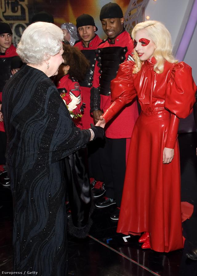 Lady Gaga 2009-ben egy puffos ujjú piros lakkruhában rázott kezet II. Erzsébet királynővel Londonban.