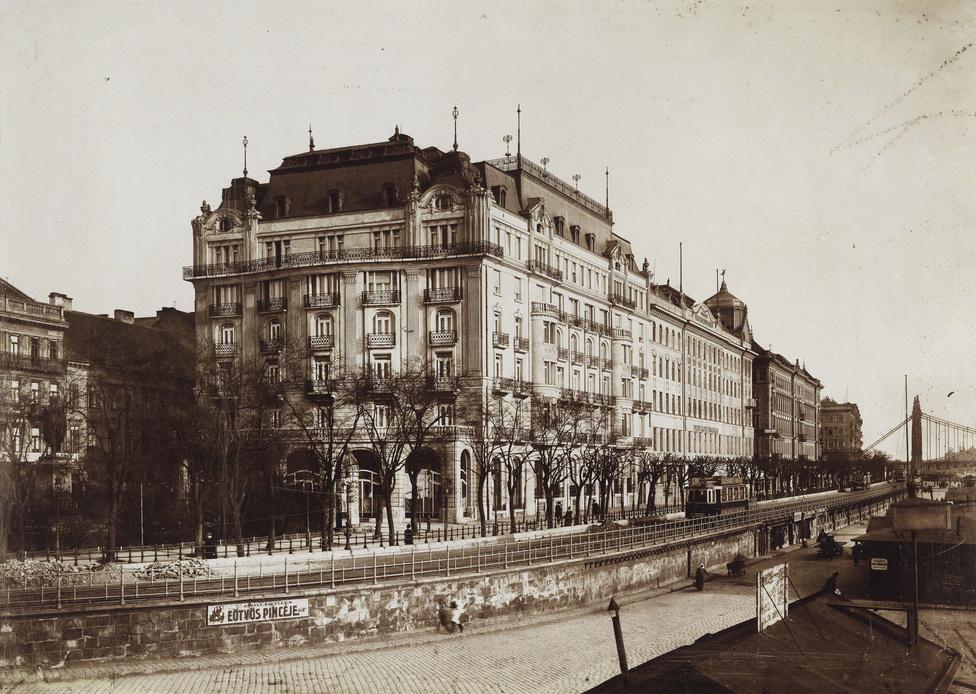 A bezárt Grand Hotel Ritz, a későbbi Dunapalota és a pesti rakpart a Lánchíd felől nézve. A szálló állandó lakója volt például az a gróf Pálffy-Daun József is, aki túlélte a 22 ember életét követelő biatorbágyi merényletet is, de megszállt itt sokak közt VIII. Edward, Nagy-Britannia és Írország királya, illetve India császára, továbbá az egyik kapurthalai maharadzsa is. A távolban az Erzsébet híd, balra pedig Eötvös József szobra látható.