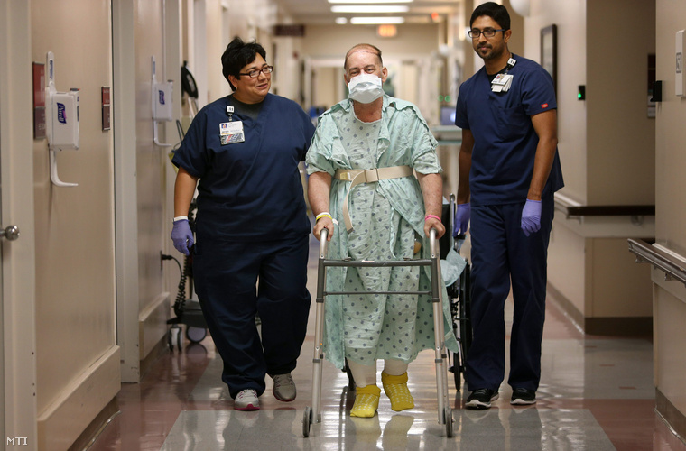 Jim Boysen 55 éves amerikai szoftverfejlesztő Gini Tagle (b) és Regi Mathew (j) fizikoterapeutákkal gyakorolja a járást a Houstoni Metodista Kórházban