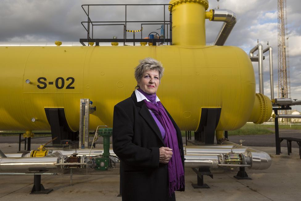 """Hajdú Ferencné Kati, gáz- és termékelszámolóként, több mint harminc évet töltött a telepen. """"Engem ez a hölgy valamiért a beatkorszakra emlékeztetett, úgyhogy nagyon örültem, amikor megtaláltam ezt a sárga tengeralattjáróra emlékeztető tartályt"""" – mesélt a fotós a kép születéséről."""