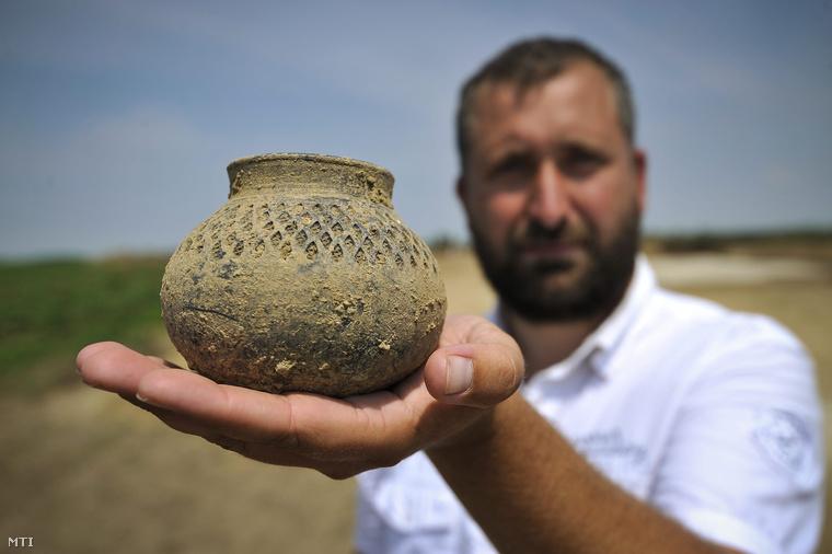 Bepecsételt díszű korongolt edényt tart kezében az épülő M4-es autópálya nyomvonalán zajló régészeti feltáráson Berettyóújfalu térségében.