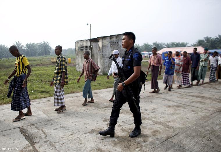 Rohingya menekülteket vezet egy indonéz rendőr egy helyi menekülttáborban.