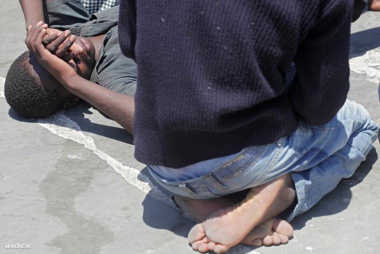 Lampedusára érkezett, kimerült menekültek a kikötő aszfaltján