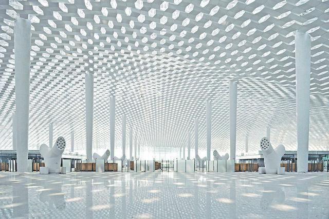 """A több éves városfejlesztési project részeként megépült terminál Kína leggyorsabban növekvő városának harmadik repülőtere. """" A perforált, kétrétegű bőrnek köszönhetően érdekes fény és árnyék játék alakul ki a barlangszerű épület belsejében. """" – mondják az építészek a masszív acél szerkezetes épületről."""