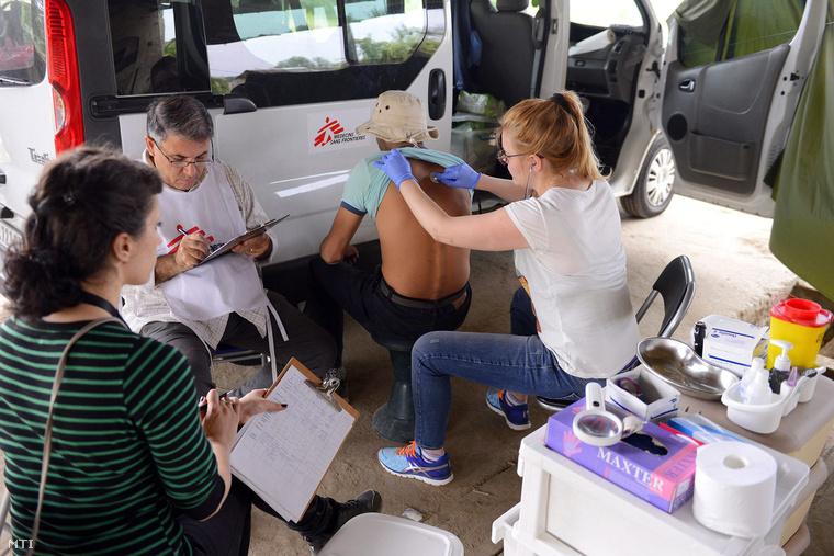 29. Az Orvosok Határok Nélkül segélyszervezet munkatársai egy afgán migránst vizsgálnak a város szeméttelepe és a régi romos téglagyár között fekvő elhagyatott területen a szerbiai Szabadka határában