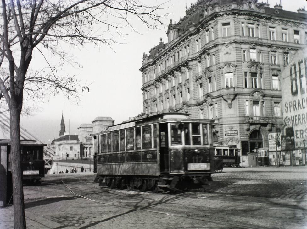 Villamosok suhannak a mai Belgrád rakparton, a távolban az Erzsébet híd és az ortodox templom tornya a Petőfi téren. Az Irányi utca sarkán még csak egy tűzfal van az 1911-ben emelt ház helyén, de az 1903-ban épített bérház már áll.