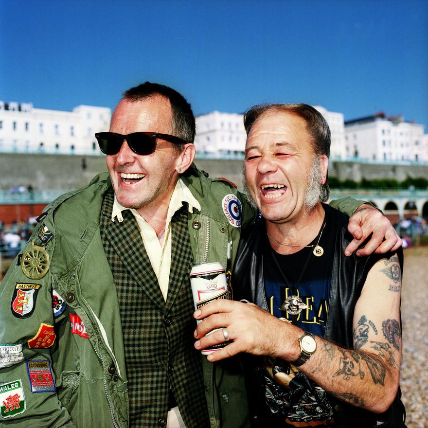 Ray Howard és Steve Cook a brightoni parton. Ray a mod szubkultúra tagja tinédzserkora óta, manapság már korára utalva Jurassic modként emlegetik az Odd Mod Squad Scooter Clubban, amelynek a tagja. A modok az 1960-as években Londonban létrejött szubkultúra, amely a hippikkel szemben határozta meg magát, egyik jellegzetességük a robogózás.                          Raynek és Steve-nek egyébként semmi közük egymáshoz, a kép készültekor látták egymást először.