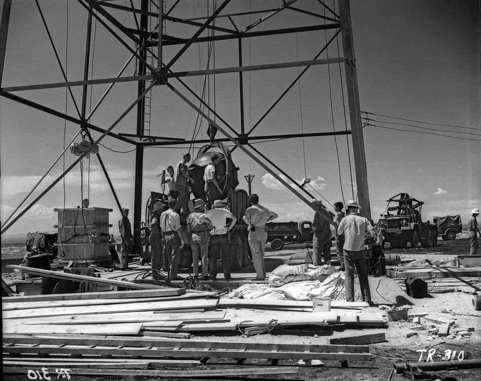 1945. július 13-a: épp a plutóniummagot helyezik be a bomba külső, robbanóanyaggal töltött köpenyébe. A dolog nem ment egyszerűen, mert a mag először megszorult, de miután kicsit hagyták kiegyenlítődni a két rész hőmérsékletét, végül minden a helyére került. A munkálatokban részt vevők ekkor nagyon megnyugodtak, és lazításképp úsztak egyet a közeli víztározó toronyban.