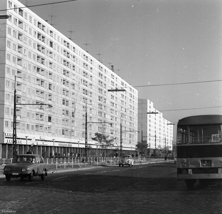 """Óbudán ekkor már tucat számra emelkedtek a tízemeletes házgyári épületek – például a Szentendrei út belső szakaszán. Látszik, hogy újak még a házak, egyik erkély sincs még beépítve. A lakások kicsik voltak ugyan, de volt meleg víz és távfűtés. A fűtést a lakásokban akkoriban még nem lehetett szabályozni, csak ablaknyitással. A hátsó részen kevés autó parkolt. Látnivaló, hogy a ma rémisztően nagy forgalmú úton milyen kevés autó jár. A földszinten csak néhány, nagy alapterületű nagy állami  lánc boltja található. A """"kisvállalkozási forradalom"""" csak tíz év múlva kezdődik majd. A Szentendrei út, a fényképen jól látható módon még macskaköves volt akkoriban. A világítást neoncsövek szolgáltatták."""