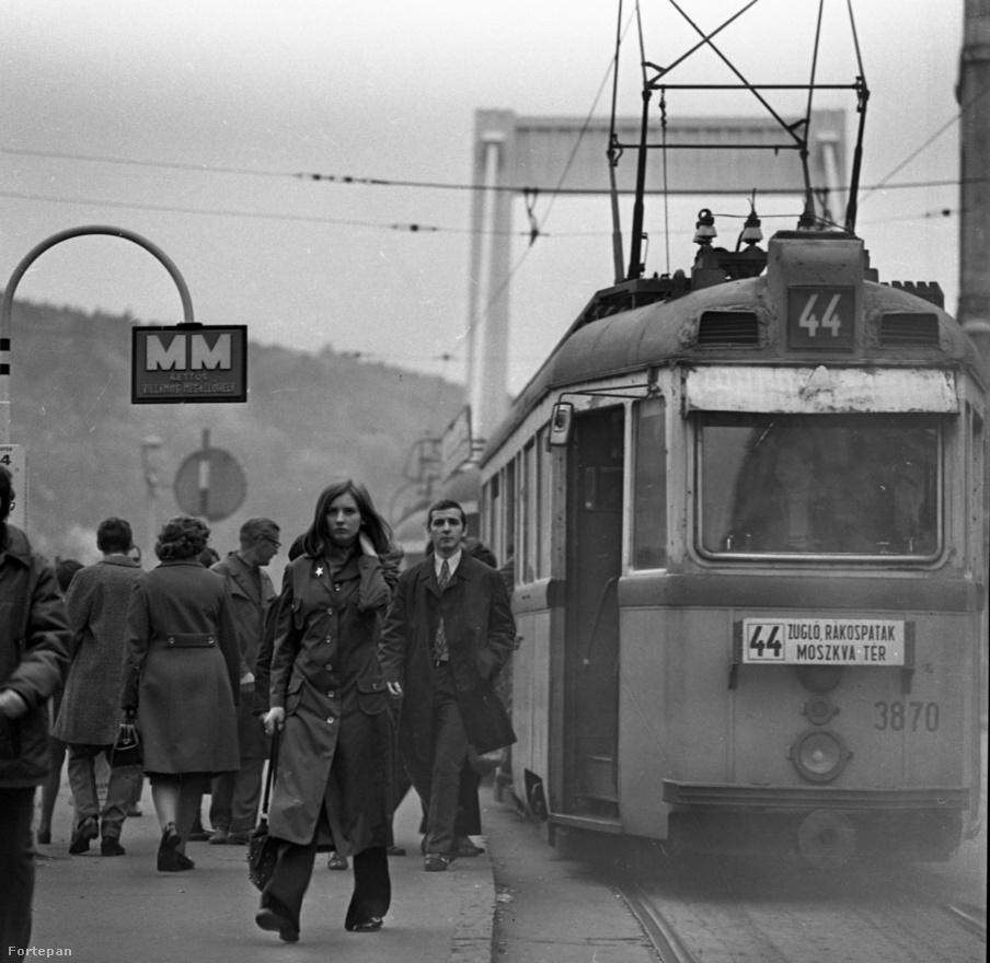 """Azt, hogy ez a kép nem 73-ban, hanem előző évben készült, onnét is tudhatjuk, hogy a villamosközlekedés a hídon 1972. december 22-én megszűnt. A síneket felszedték, helyükre harmadik autósáv épült. Akkor jó ötletnek, a világvárosi fejlődés újabb állomásának érezték a fiatalok is. A 44-es villamoson már a lépcsőn se lehetett utazni – a szerelvény addig nem indult, amíg az ajtók be nem csukódtak. Ezek az ún. """"stuka"""" villamosok már a negyvenes évek elején szolgálatba álltak, ekkoriban ez volt az átlag: se új, se régi hatást nem keltett. A kép inkább reggeli, mintsem esti jelenetet mutat. A diáklányon (bolti eladón?) és a snájdig tisztviselőn (művezetőn?) inkább valami várakozás, semmint fáradtság vagy elkínzottság látható.                         Átlagos év volt ez a Kádár rendszerben. A villamoson már rég nincs vörös                          csillag, az utca emberének fogalma sincs arról, hogy a szovjet elvtársak                          most parancsolnak megálljt az Új Gazdasági Mechanizmusnak, és ez egy                          hosszú és nyomasztó stagnálás nyitánya lesz."""