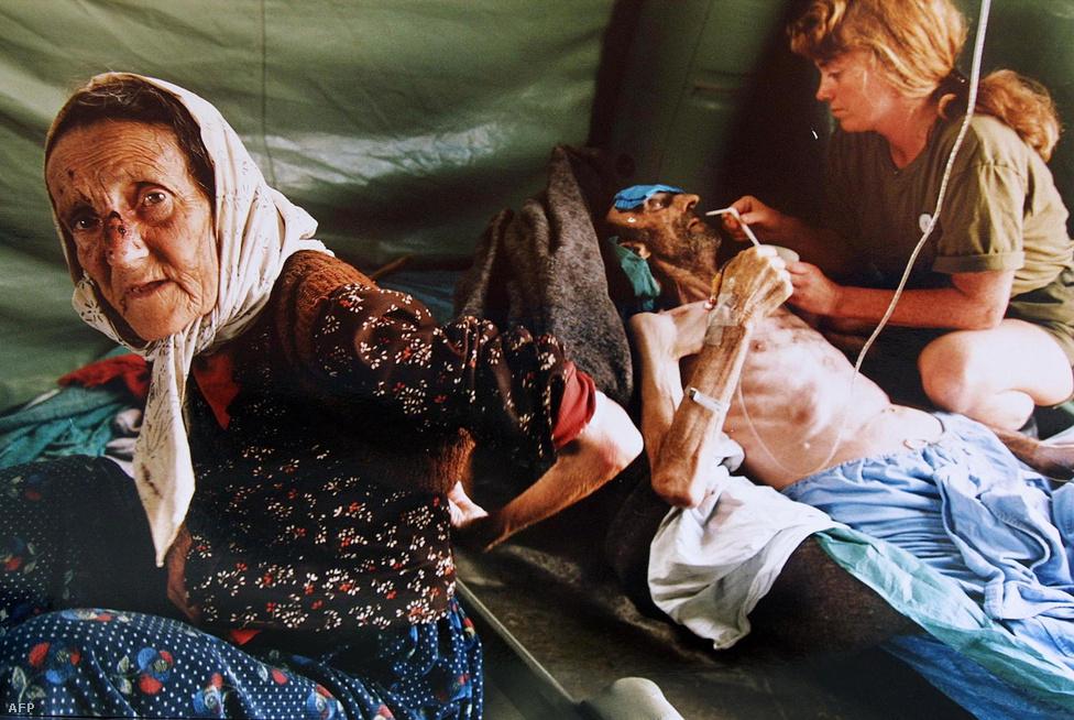 Ez a kép 1995 július 11-én készült. Az idős nő és a hosszú idő óta éhező férje megsérültek a szerbek srebrenica elleni támadásaiban.                         Akik tudtak, a még nem lerombolt bosnyák városokba menekültek a hadsereg kegyetlensége elől. Srebrenica lakossága ezért egy-két év alatt kilenc ezerről 42 ezerre duzzadt. A városban már kezdetektől ostromkörülmények uralkodtak: a legtöbb menekült az utcán, bármiféle fedezék nélkül húzta meg magát, miközben folyamatosa volt szerbek tüzérségi támadása, alig volt víz és áramot is csak a házilag buherált generátorok termeltek. Az emberek éheztek, mindennapos volt az erőszak, virágzott a prostitúció és a fekete piac. 1993-ban Srebrenicában a járt az ENSZ jugoszláviai békefenntartóinak (UNPROFOR) a vezetője, a francia Philippe Morillon és egy lakossági gyűlésen azt mondta, nem kell aggódni, a város az ENSZ védelme alatt áll és az ENSZ sosem fogja cserben hagyni a srebrenciaiakat.