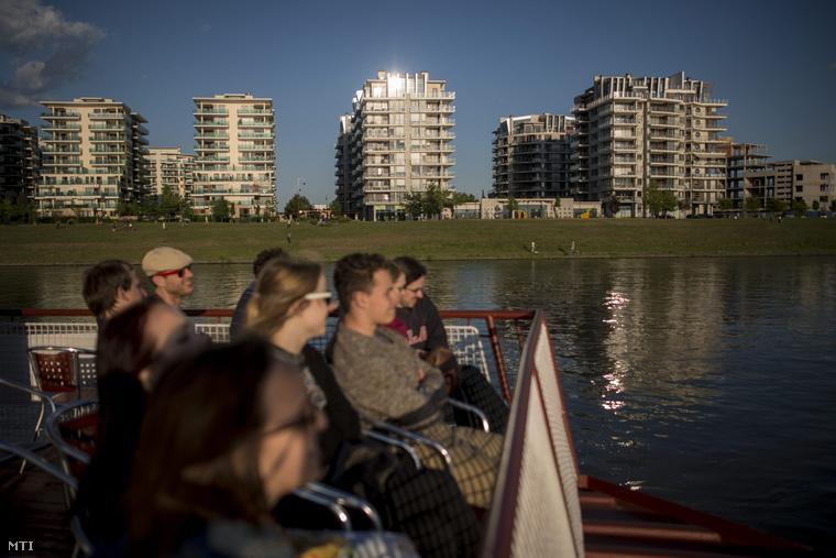 Turisták a BKK hajóján utaznak a Duna fővárosi szakaszán, háttérben a Marina Part lakópark házai 2015. május 11-én.