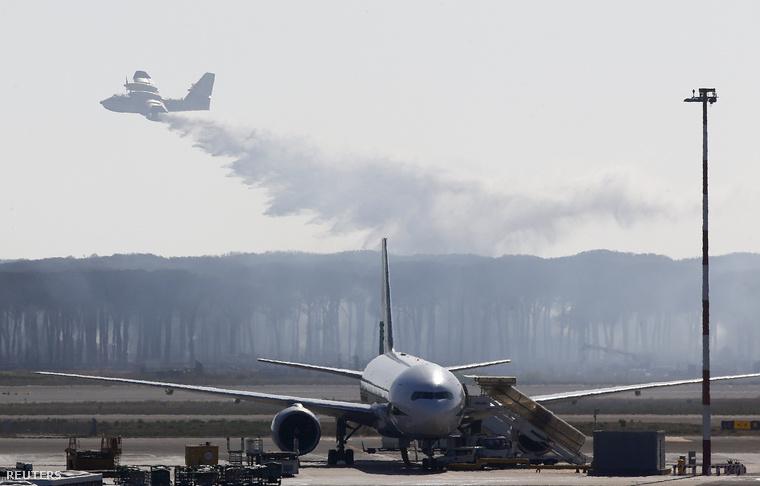 A Canadair tűzoltó repülőgépe oltja az erdőt a Fiumicino nemzetközi repülőtér közelében, Rómában.