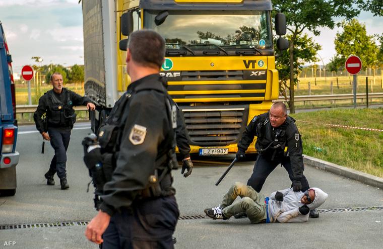 Francia rendőr próbál megállítani egy migránst a Csalagútnál, Calais közelében, 2015. július 30-án.