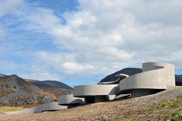 """A norvég Reiulf Ramstad Architects a szeles Jeges-tenger partjára tervezte ezt a kígyózó beton rámpát. """" A Havøysund turisztikai útvonal egyike a Norvégiában bejárható 18 nemzeti turisztikai útvonalnak. A fokozatosan lejtő padló a kerekes székes látogatók számára is elérhetővé teszi a kirándulást."""" – mondja az építészstúdió."""