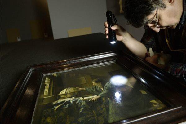 Fáy András restaurátor vizsgálja Vermeer Az asztronómus című festményét
