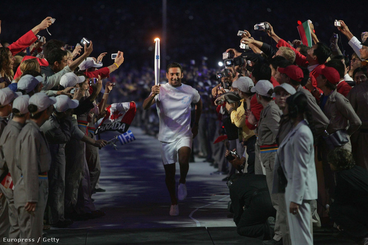 Az olimpiai láng érkezik az athéni stadionba a 2004-es olimpia nyitóünnepségén