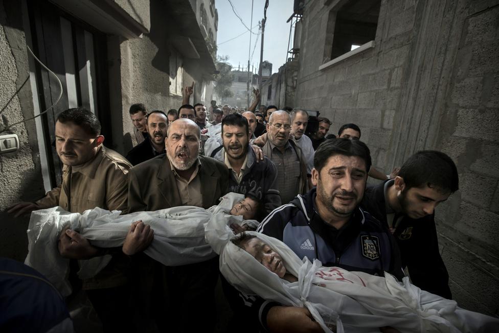 2013. A 2 éves Suhaib Hijazi és 4 éves bátyja, Muhammad holttestét viszik a családtagok a búcsúztatásra egy gázai mecsetbe.A gyerekek november 19-én haltak meg, amikor otthonukat izraeli bombatalálat érte. Apjuk, Fouad is meghalt, anyjuk és négy további rokonuk súlyosan megsérült. Izrael november 14-én indított támadást a Hamasz vezette Gázaváros ellen válaszként a palesztin fegyveres alakulatok rakétatámadásaira. A november 21-én megkötött tűzszünetig már 150 ember halt meg Gázában, a 103 polgári áldozat között legalább 30 gyerek volt.A fotó az elmúlt évek leghevesebb szakmai vitáit generálta, miután kiderült, hogy a fotós változtatott a kép tónusain, kontrasztján, sötétített a háttéren és kiemelte az arcokat a drámaibb hatás kedvéért. Bár ez bevett gyakorlat minden hasonló pályázaton, a győztes képen a tragikus téma miatt többen számon kérték az esztétizáló beavatkozást. Hónapokig tartó szakmai viták után a zsűri úgy ítélte, hogy a fotó ereje meggyőzőbb a tálalásnál, a képen végrehajtott változtatások pedig nem érintik a kép hitelességét.