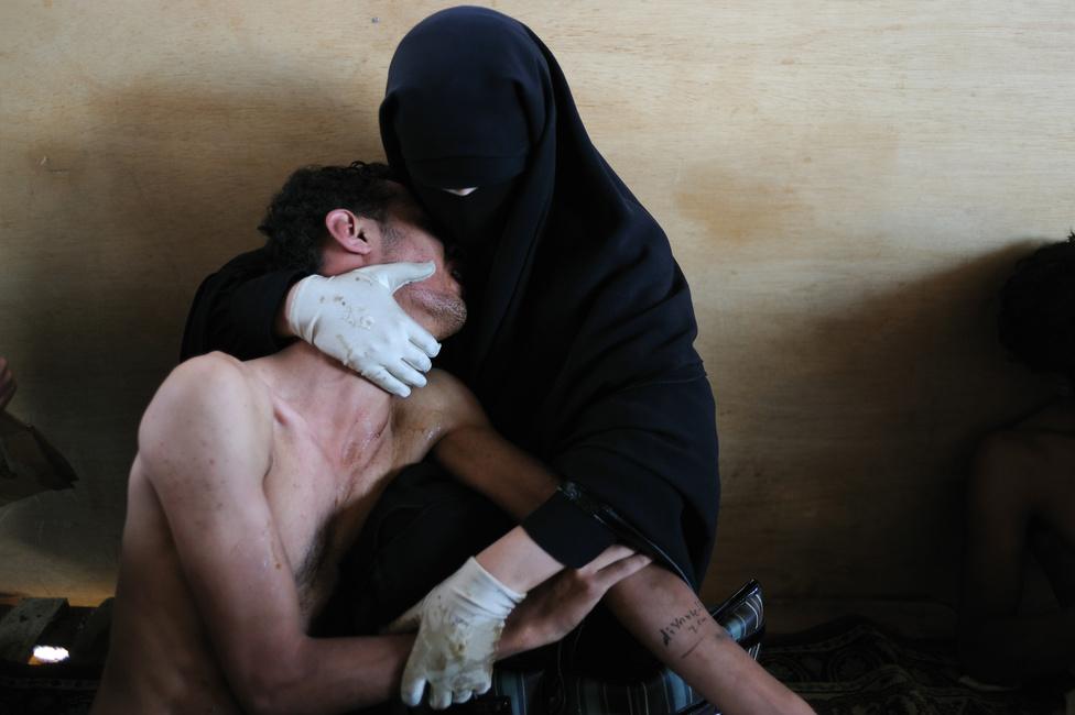 """2012. Fatima Al-Qaws és 18 éves Zayed fia, akit könnygáz kínoz az október 15-i tüntetések után.Az Ali Abdullah Saleh elnök 33 éve tartó önkényuralma ellen tiltakozó több ezres tömegre a Külügyminisztérium épületénél tüzet nyitottak. Legalább 12 ember meghalt, 30 megsebesült. Az anya, aki maga is a tüntetők közt volt, egy ideiglenes tábori kórházzá alakított mecsetben találta meg a fiát a sebesültek között. Zayed két napig kómában volt. November 23-án Saleh elnök Szaúd-Arábiába menekült és átadta a hatalmat helyettesének, Abdurabu Mansur Hadinak. A 2012. február 25-i választást követően Hadi beiktatásával formálisan is megszűnt Saleh elnök uralma.Az 55. év fotója díjat Samuel Amanda képének ítélték: könnygáztól szenvedő fiát nyugtatja az anya a jemeni fővárosban zajló tüntetések után. """"Ez a fotó a térség egészéről szól"""", fogalmazott Koyo Kouoh, a zsűri egyik tagja,"""" Jemenről, Egyiptomról, Tunéziáról, Líbiáról, Szíriáról, az Arab Tavasz összes eseményéről. A történéseknek azonban a privát, bensőséges oldalát mutatja. És megmutatja a nők szerepét is, aki nemcsak ápoltak és vigasztaltak, hanem a mozgalmak aktív részesei is voltak."""" Az összes tragédia ellenére a zs űri egy olyan képet kívánt díjazni, ami nemcsak tükrözi az év történéseit, hanem vigaszt is nyújt. Samuel Aranda fotóján a részvét id őtlen és azonnal felismerhető a világ bármely pontján."""