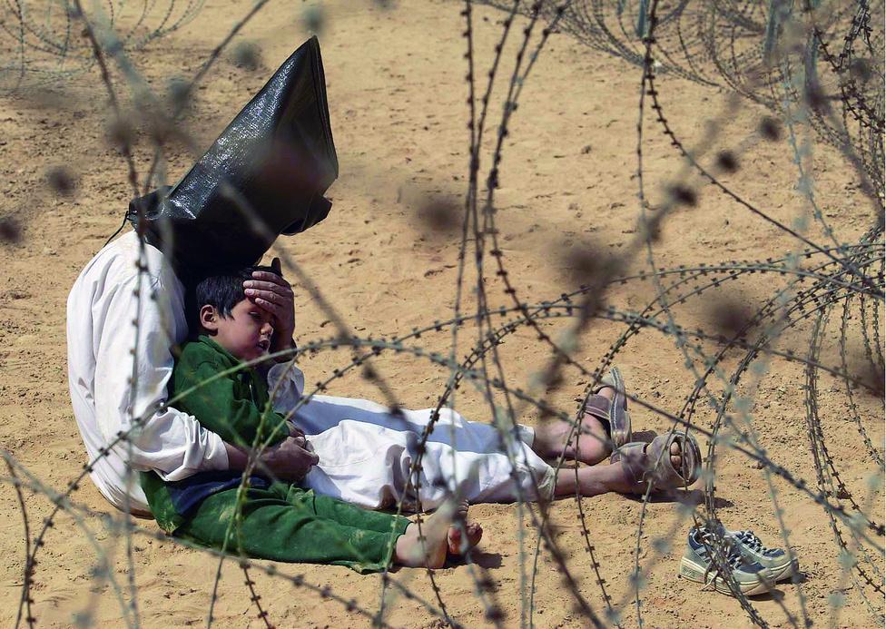 """2004. Egy iraki férfi 4 éves kisfiát nyugtatja az amerikai hadifogoly-táborban An Najaf közelében.A kisfiú megijedt, amikor apját megbilincselték és a fejére csuklyát húztak. Egy amerikai katona később levette a bilincset, hogy a férfi megnyugtathassa a fiát. A csuklyákat azért alkalmazták, mert gyorsabb volt, mint bekötni az őrizetesek szemét. A hadsereg szerint a csuklyának az a szerepe, hogy megzavarja a fogoly tájékozódását és védje személyazonosságát. Nem tudni, mi történt a férfivel és a fiával.                         Az iraki háború sokszorosan megjelent a 2004-ben versengő képeken, nyolc díjat vittek el a konfliktusról, előzményeiről és utóhatásáról készült egyedi fotók és képsorozatok.Jean-Marc Bouju képére azért esett a választás, mert """"érzékelteti a háború rettenetes hatását a hétköznapi életre függetlenül attól, hogy éppen miért is robbant ki"""", fogalmazott a zsűri elnöke                         Elisabeth Biondi                         Bouju fotója volt az első digitálisan készült év képe."""